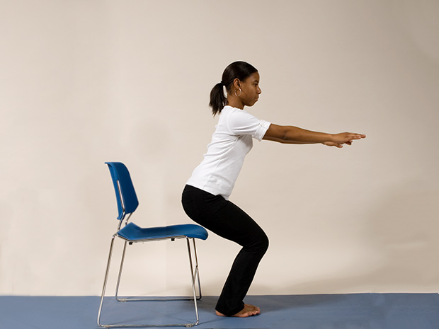 Model demonstrates step 2 of the chair squat exercise